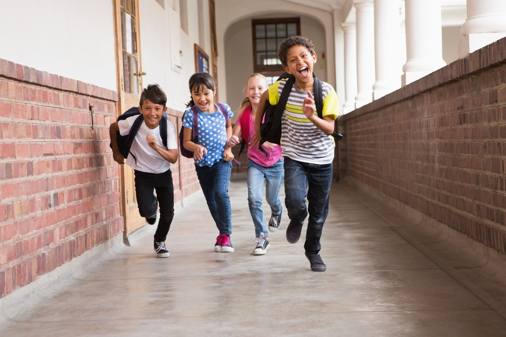 Cute pupils running down the hall at the elementary school.jpeg